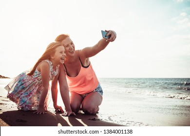 Mother and daughter taking selfie with mobile smartphone while playing on tropical beach at sunset - Happy family having fun with new technology apps for social media - Parenthood concept