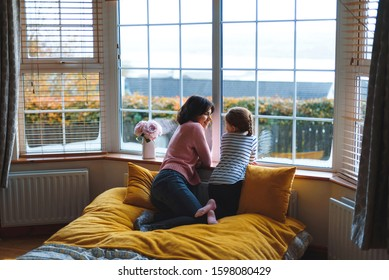 mother and daughter talking to each other at big window