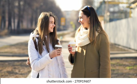 Mother and daughter talking, laughing and smiling on the street, drinking coffee in cups, in the fall or spring day, happy family.