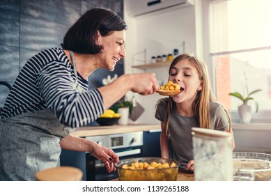 Mother and daughter tasting apple pie filling in the kitchen