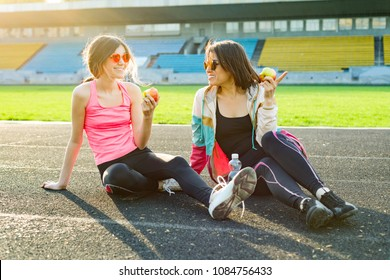 Mother and daughter teenager resting after workout at stadium. Healthy lifestyle and food, drink water, eat apples