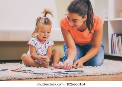 Mother and daughter in their home. They are looking at coloring book.