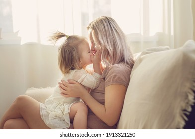 Mother and  daughter toddler playing, kissing, hugging  and smiling, enjoy at the sofa, spending time at home. Moments of tenderness . Happy loving family. Good time at home. Family single mother