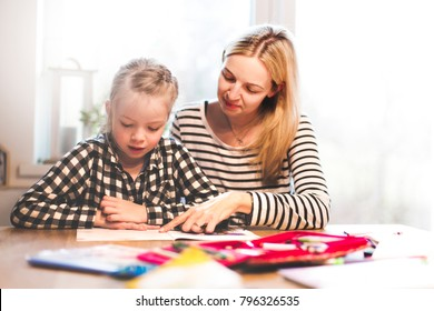 mother and daughter togehter doing schoolwork at home