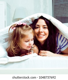 mother with daughter together in bed smiling, happy family close