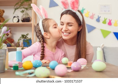 Mother and daughter together at home easter preparation in bunny ears sitting girl kissing mom