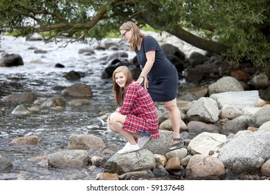 Mother and daughter together located with a wonderful stony coast