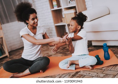 Mother and Daughter Together Traning. Studio with Family. Mother Help Little Girl with Hand. Happy Family Training in Studio. Sportwear for Little Girl and Young Mother. Relaxation DAy with Young Mom.