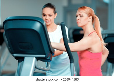 Mother and daughter training. Beautiful mature woman and her teenage daughter in sports clothing exercising on elliptical cross trainer in the gym