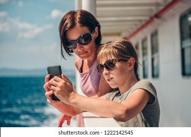 Mother and daughter traveling on ferry and taking pictures with smart phone at ship deck