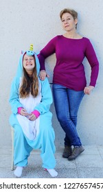 Mother with daughter in a unicorn costume. Strange family, teen problems
