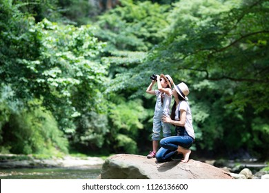 Mother and daughter using binoculars