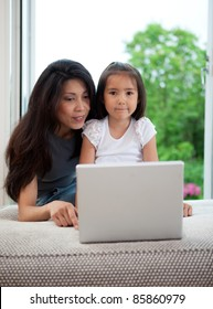 Mother and daughter using computer together in a home interior
