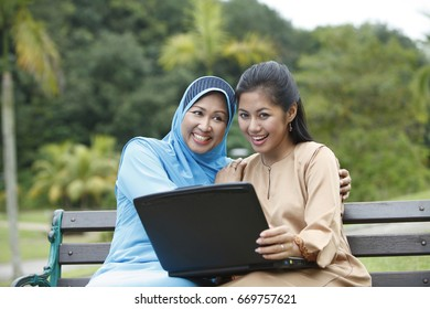 Mother and daughter using laptop.