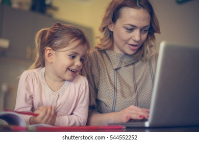 Mother with daughter using laptop in the kitchen.