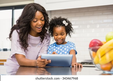Mother and daughter using tablet pc in the kitchen