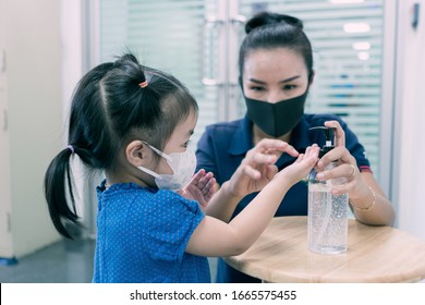 A mother and daughter using wash hand sanitizer gel pump dispenser, Washing hand with Alcohol Sanitizer, prevent the virus and bacterias, Hygiene and Covid-19 virus protection concept.