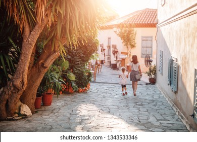 Mother and daughter walkin along mediterranean old city streets in the summer during vacation