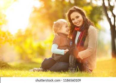 Mother and daughter walking in the autumn park. Beauty nature scene with colorful background, yellow trees and leaves at fall season. Autumn outdoor lifestyle. Happy family relax on green grass
