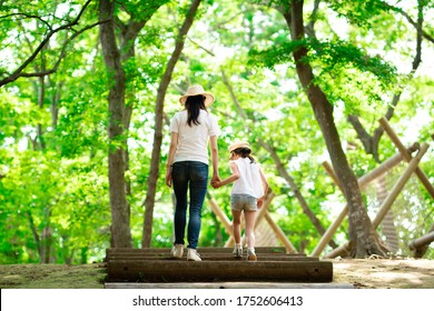 Mother and daughter walking hand in hand in forest stairs