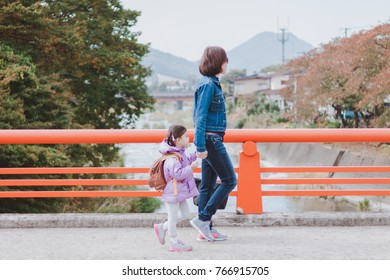 Mother and daughter walking hand in hand on holidays in Japan