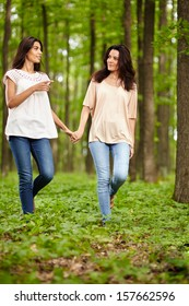 Mother and daughter walking hand in hand through a forest and talking
