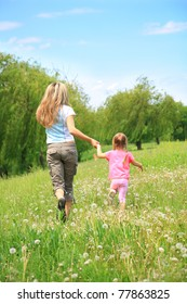 Mother and daughter walking on path holding hands