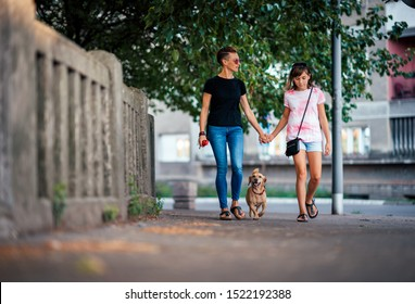 Mother and daughter walking on the street with a small brown dog and holding hands