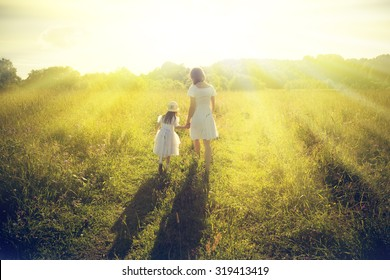 Mother and daughter walking on the sunny meadow.