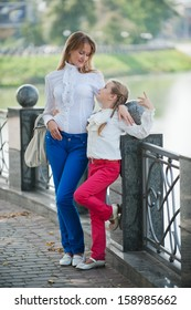Mother and daughter walking in the summer park