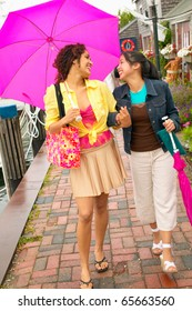 Mother and daughter walking with umbrella