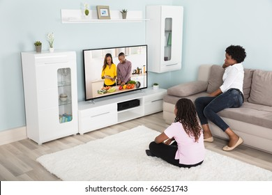 Mother And Daughter Watching Enjoying Watching Television At Home