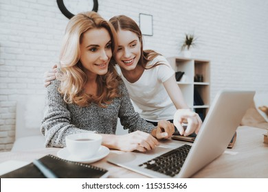 Mother and Daughter Watching into Laptop at Home. Daughter Helping Mother. Mother and Daughter at Home. Teenage Girl. Frilancing Mother Concept. Women Using Digital Device. Smiling Woman.