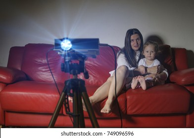 Mother and daughter watching a movie at home with the projector