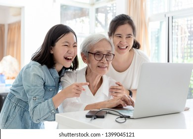 Mother and daughter watching something interesting with grandmother,happy smiling asian senior woman while her daughter and granddaughter using laptop computer at home,concept family,technology
