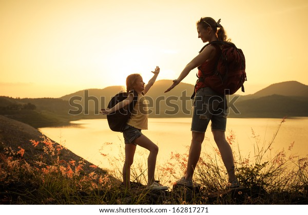 Mother and daughter  watching the sunset on the lake