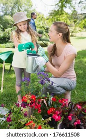 Mother with daughter watering plants at the garden