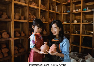 mother and daughter wearing apron and holding pottery goods made from clay