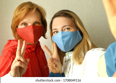 Mother and daughter wearing  cotton cloth hand made face mask at home during quarantine. Family selfie. Protect against coronavirus. Bokeh effect.