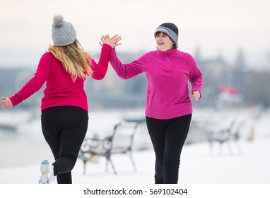 Mother and daughter wearing sportswear and running on snow during winter