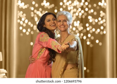 mother and daughter wearing traditional clothing, embracing while posing happily together interacting on diwali festival