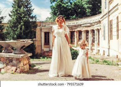 Mother and daughter in wedding dress have a nice time outdoor in green summer park. Happiness, beauty, fashion concept