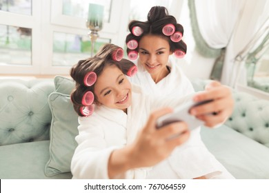 Mother and daughter in white bathrobes are sitting on the couch. They have curlers in their hair. My daughter and mother making selfie.