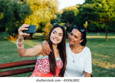 Mother and daughter women using a mobile phone in the park