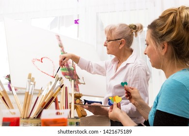 Mother and daughter work together on a painting