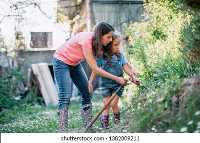 Mother and daughter working in the garden with gardening equipment