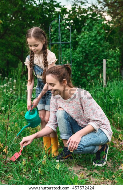 Mother and daughter working in the garden. Little girl and young woman engaged in gardening. Planting, weeding and watering the plants.