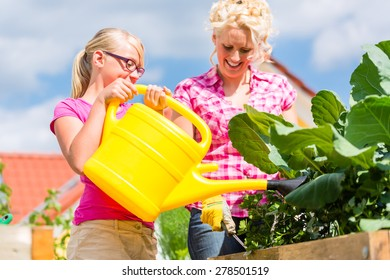 Mother and daughter working in garden watering plants with can in front of their house
