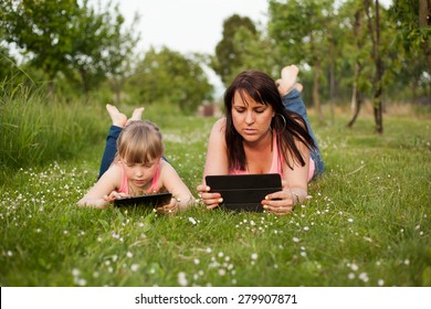 Mother and daughter working on a tablet.