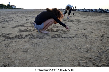 mother and daughter writing into a sand on the beach